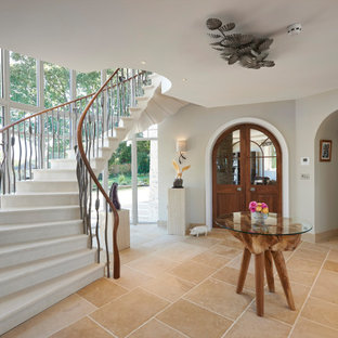 Photo of a classic foyer in Surrey with grey walls and beige floors.