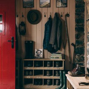 Ispirazione per un ingresso country con pareti marroni, una porta singola, una porta rossa e pavimento grigio