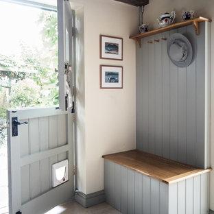 Immagine di un ingresso con anticamera country con pareti bianche, una porta olandese, una porta grigia e pavimento grigio