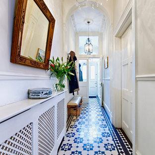 Esempio di un corridoio chic di medie dimensioni con pareti grigie, pavimento con piastrelle in ceramica, una porta a due ante e una porta bianca