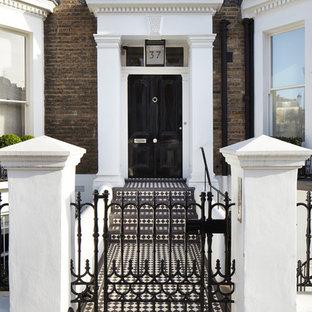 Exempel på en klassisk ingång och ytterdörr, med klinkergolv i keramik, en enkeldörr och en svart dörr