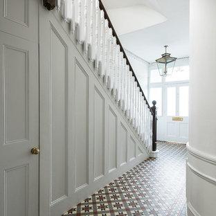 ロンドンの中くらいのトラディショナルスタイルのおしゃれな玄関 (白い壁、セラミックタイルの床、マルチカラーの床) の写真