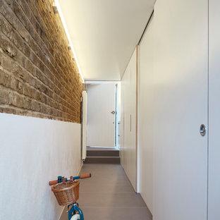 Exemple d'une petit porte d'entrée moderne avec un mur blanc, béton au sol, une porte simple, une porte noire, un sol gris, un plafond voûté et un mur en parement de brique.