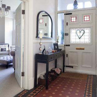 ロンドンの片開きドアヴィクトリアン調のおしゃれな玄関ドア (緑の壁、白いドア、テラコッタタイルの床) の写真