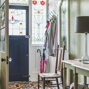 Inspiration pour un vestibule victorien avec un mur vert, un sol en bois brun, une porte simple et une porte noire.