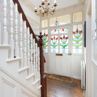 Entryway - small victorian medium tone wood floor entryway idea in London with white walls and a white front door