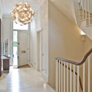 Elegant white floor entryway photo in London with a white front door