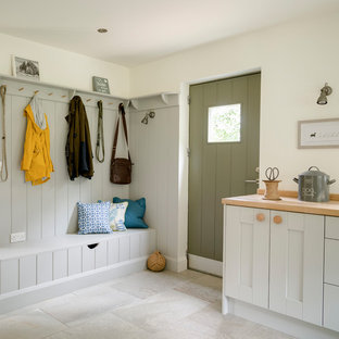 This is an example of a farmhouse boot room in West Midlands with white walls, a single front door, a green front door and beige floors.