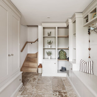 This is an example of a medium sized classic boot room in Other with white walls and grey floors.