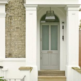 Modelo de puerta principal tradicional, de tamaño medio, con puerta simple, puerta gris y paredes marrones