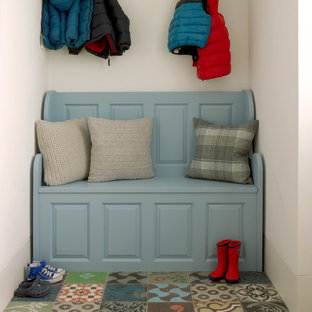 This is an example of a traditional mudroom in London with white walls and multi-coloured floor.