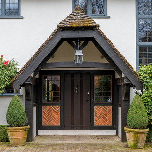 Inspiration for a farmhouse front door in Surrey with white walls, a single front door, a dark wood front door, brick flooring and brown floors.
