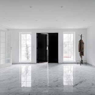 Inredning av en minimalistisk entré, med marmorgolv, en dubbeldörr och en svart dörr