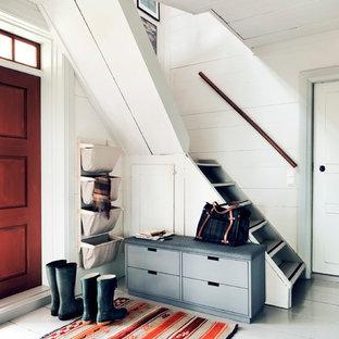 Lantlig inredning av en foajé, med vita väggar, målat trägolv, en enkeldörr och en röd dörr