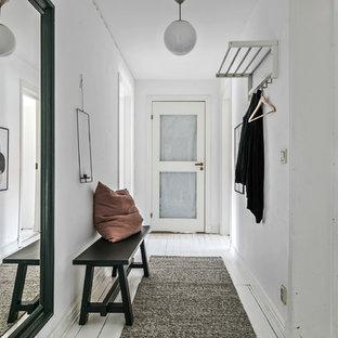 Minimalistisk inredning av en hall, med vita väggar, målat trägolv, en enkeldörr, en vit dörr och vitt golv
