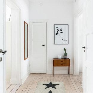 Foto på en stor minimalistisk hall, med ljust trägolv, en enkeldörr, en vit dörr och vita väggar