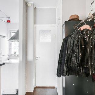 Inspiration för minimalistiska ingångspartier, med grå väggar, en enkeldörr, en vit dörr och brunt golv