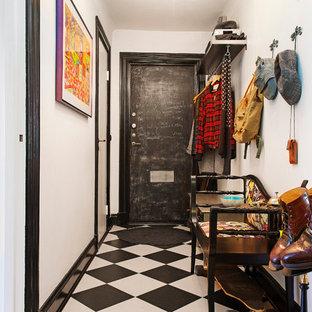 Cette image montre une entrée bohème de taille moyenne avec un couloir, un mur blanc, une porte simple, une porte noire et un sol en carrelage de céramique.