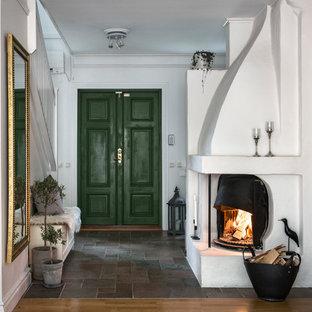 Klassisk inredning av en mellanstor hall, med vita väggar, grått golv, en dubbeldörr och en grön dörr
