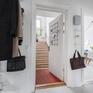 Inredning av en nordisk liten entré, med laminatgolv, vita väggar och vitt golv