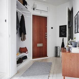 Skandinavisk inredning av ett kapprum, med vita väggar, målat trägolv, en enkeldörr, vitt golv och mellanmörk trädörr
