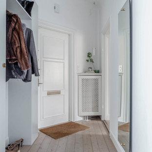 Exempel på en mellanstor minimalistisk entré, med vita väggar och ljust trägolv