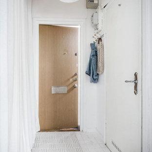 Bild på en liten minimalistisk hall, med vita väggar, en enkeldörr, ljus trädörr och vitt golv