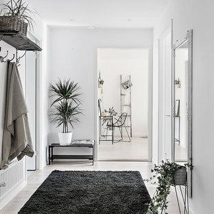 Стильный дизайн: вестибюль среднего размера в скандинавском стиле с белыми стенами, светлым паркетным полом и одностворчатой входной дверью - последний тренд