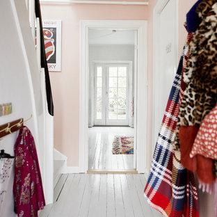 Aménagement d'une petit entrée scandinave avec un mur rose, un sol en bois peint et un sol blanc.