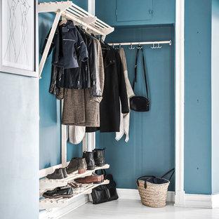 Skandinavisk inredning av ett mellanstort kapprum, med blå väggar, målat trägolv och vitt golv