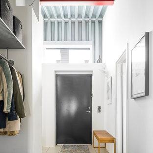 Idéer för industriella hallar, med vita väggar, en enkeldörr, en svart dörr och beiget golv