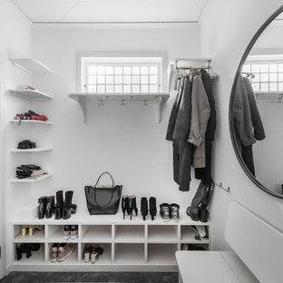 Minimalistisk inredning av ett mellanstort kapprum, med vita väggar och svart golv