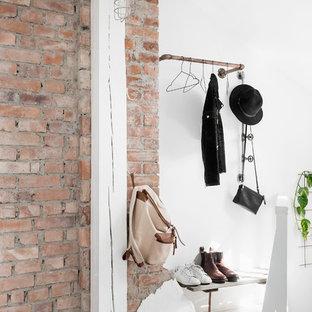 Nordisk inredning av en liten entré, med vita väggar och ljust trägolv