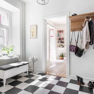Aménagement d'une entrée scandinave de taille moyenne avec un couloir, un mur blanc, un sol en linoléum et un sol noir.
