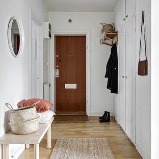 Inspiration för skandinaviska hallar, med vita väggar, ljust trägolv, en enkeldörr, mellanmörk trädörr och beiget golv