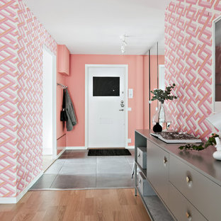 Foto på en minimalistisk entré, med vita väggar, en enkeldörr, en svart dörr och grått golv