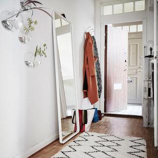 Inredning av en skandinavisk liten entré, med vita väggar, mellanmörkt trägolv och brunt golv