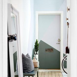 Idéer för mellanstora minimalistiska hallar, med flerfärgade väggar, ljust trägolv och en enkeldörr