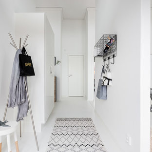 Scandi hallway in Gothenburg with white walls, a single front door, painted wood flooring, a white front door and white floors.