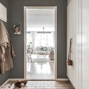 Minimalistisk inredning av ett mellanstort kapprum, med grå väggar, tegelgolv, en enkeldörr, en vit dörr och brunt golv