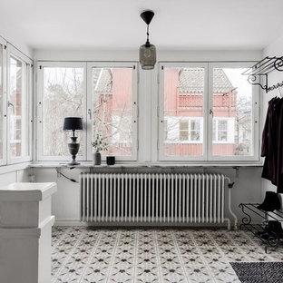 Foto på en mellanstor nordisk foajé, med vita väggar, flerfärgat golv, en enkeldörr och en vit dörr