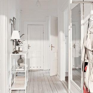 Skandinavisk inredning av en hall, med vita väggar, ljust trägolv, en vit dörr, vitt golv och en enkeldörr