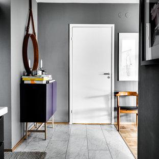 Bild på en mellanstor skandinavisk entré, med vita väggar och ljust trägolv
