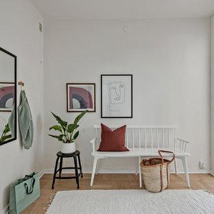 Idéer för att renovera en skandinavisk foajé, med vita väggar, ljust trägolv och beiget golv