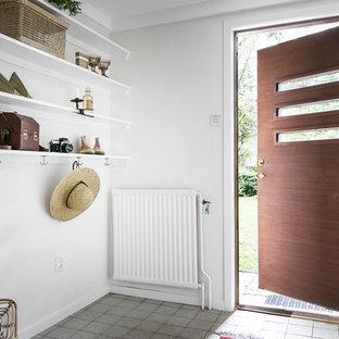 Idéer för nordiska foajéer, med vita väggar, en enkeldörr, mellanmörk trädörr och grått golv