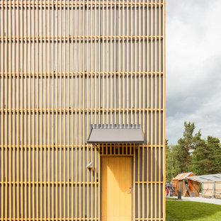 Idée de décoration pour une porte d'entrée nordique de taille moyenne avec un mur jaune, béton au sol, une porte simple et une porte jaune.