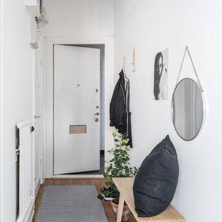 Exempel på en mellanstor nordisk hall, med vita väggar, ljust trägolv, en enkeldörr och en vit dörr