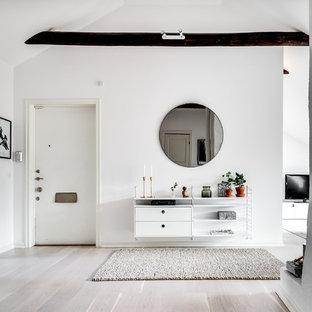 Inredning av en skandinavisk mellanstor entré, med vita väggar och grått golv