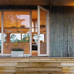 Aménagement d'une petit porte d'entrée scandinave avec un mur marron, un sol en bois brun, une porte simple et une porte en verre.