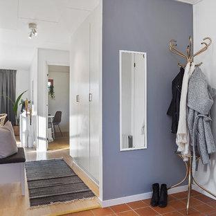 Inspiration för en nordisk hall, med lila väggar, klinkergolv i terrakotta, en enkeldörr, en vit dörr och brunt golv